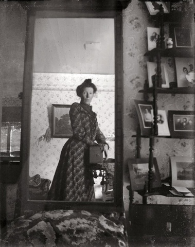 An Edwardian lady using a mirror in her home to take a selfie using an old Kodak Brownie box camera in the early 1900's.