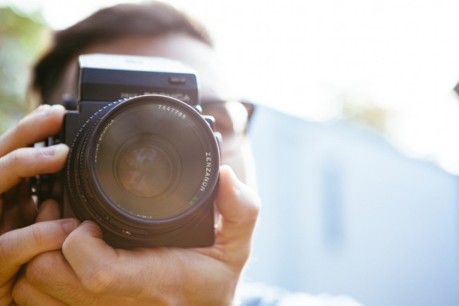 holding a DSLR camera and taking a picture with the Nikon 7000 video.