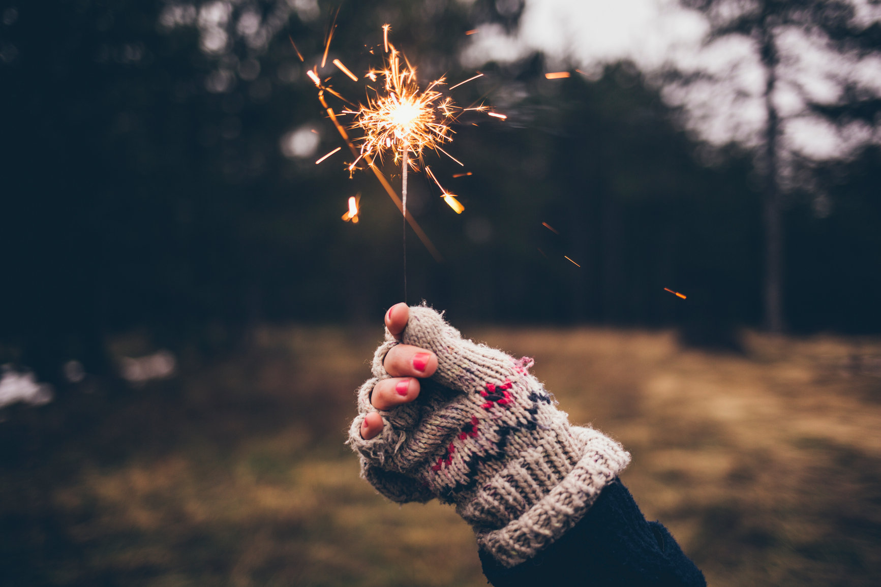 Woman holding a sparkler on a cold winter day.