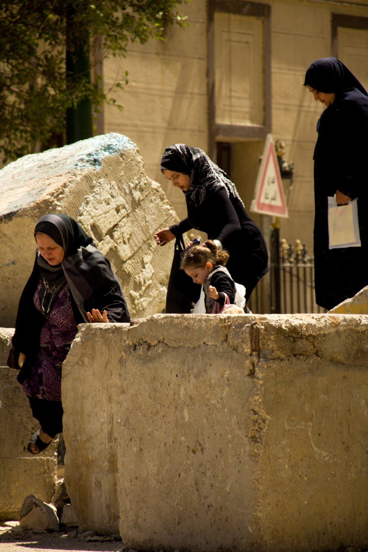 Egyptian women climb over rubble